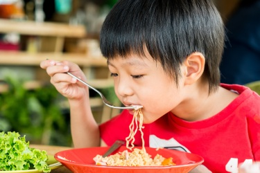 image of asian boy eating noodles
