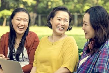 Asian American women laughing at park