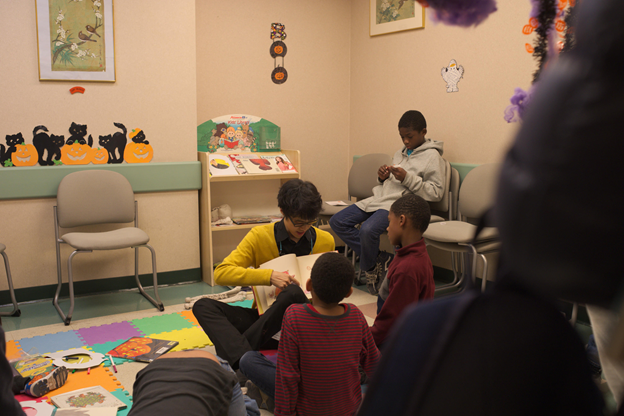 Man reads book to two children at Halloween event.