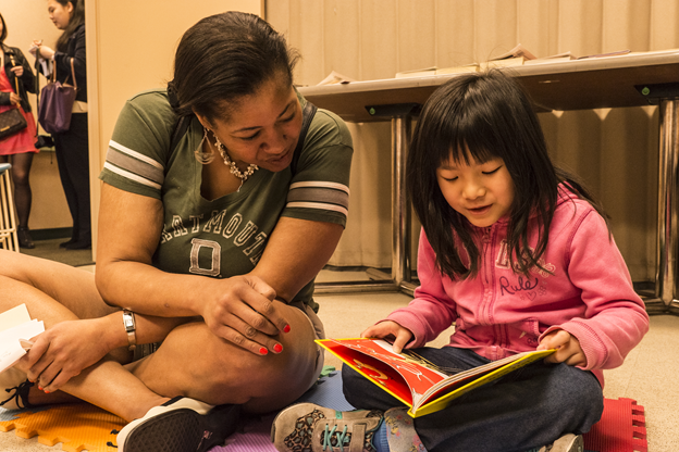 Woman reading book with child.